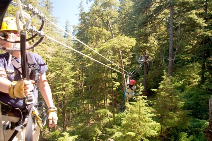 """Ketchikan, USA - August 12, 2010. A female zip line attendant awaits the next adventurer at the Alaskan Canopy Adventures, a popular excursion for the many cruise ships that dock there. A mature woman zips into the background."""