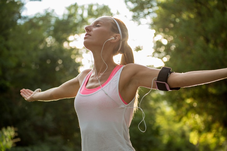 Beautiful and sporty young woman listening to music while stretching after jogging outdoors. Arms outstretched for positive emotion.