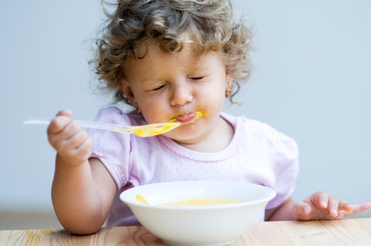 Girl eating baby food, close-up