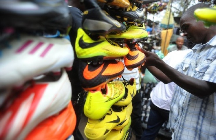 """A shopper looks at football shoes displayed in Gikomba Market, East Africa's biggest second-hand clothing market, on July 10, 2014 in Nairobi. Locally known as """"Mitumba"""", second-hand clothes trade has developed from mainly international charitable donations to become a bustling business sector. AFP PHOTO/SIMON MAINA (Photo credit should read SIMON MAINA/AFP/Getty Images)"""